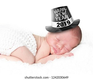 Portrait of a newborn baby wearing a Happy New Year tophat, 2019, sleeping on a white blanket.