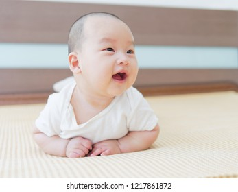 Portrait of newborn Chinese baby child relaxing in bed after bath or shower. Looking aside with happy and smile expression. Textile and bedding for kids.
