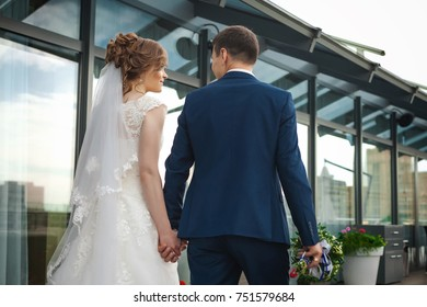 portrait of newlywed couple. back view of beautiful bride in white wedding dress and asian groom in dark blue suit