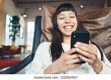 Portrait of nice asian woman with mobile phone sitting in leather chair in big loft apartment and smiling