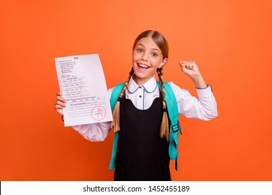 Portrait of nice attractive charming cute smart clever cheerful cheery successful glad pre-teen girl demonstrating great cool best grade having fun isolated on bright vivid shine orange background