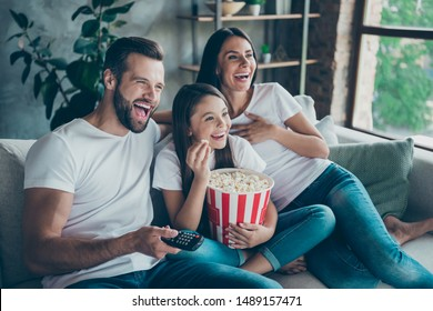 Portrait of nice attractive lovely positive glad cheerful cheery family wearing casual white t-shirts jeans denim sitting on sofa having fun watching funny video enjoying spending free time