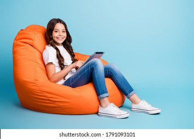 Portrait of nice attractive lovely pretty smart cheerful wavy-haired girl sitting in chair using reading ebook isolated on bright vivid shine vibrant blue teal turquoise color background