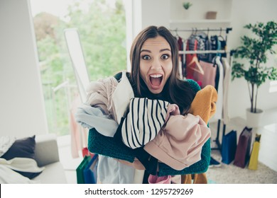 Portrait of nice attractive pretty funny shocked girl student holding pile many different things in hands screaming loudly in light white interior room