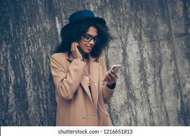Portrait of nice cheerful cute sweet lovely charming curly-haired lady wearing cosy beige spring season cashmere topcoat outfit eyeglasses eyewear listening audio podcast phone