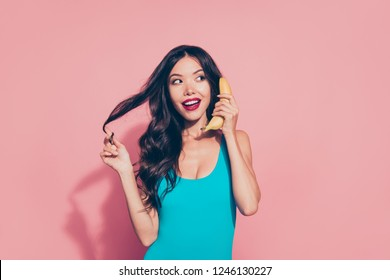 Portrait of nice cheerful funky playful cute attractive charming adorable wavy-haired lady red lips holding banana like phone talk speak chat conversation isolated over pink pastel background