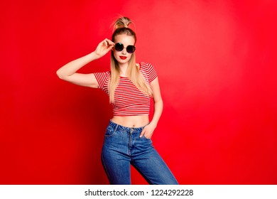 Portrait of nice cool cocky lovely glamorous charming attractive slim fit thin girl with pigtail pony-tail touching sun glasses isolated over bright vivid red background