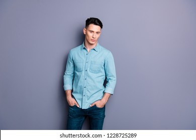 Portrait of nice cute calm attractive well-groomed handsome man wearing blue formal shirt jeans holding hands in pockets isolated over pastel violet background