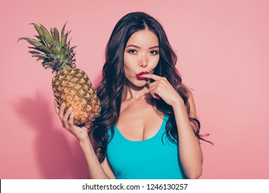 Portrait of nice cute flirty cunning foxy girlish adorable attractive charming gorgeous wavy-haired lady red lips licking finger holding ananas in hands isolated over pink background