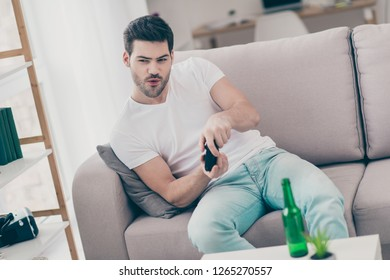 Portrait of nice cute handsome attractive bearded brunet guy sitting on divan playing videogame having fun lonely single party in white light modern interior room