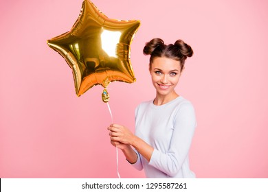 Portrait of nice cute lovable adorable attractive lovely cheerful cheery positive girl holding big air baloon golden star isolated over pastel pink background
