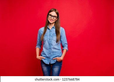Portrait of nice cute lovely attractive adorable charming cheerful cheery positive girl wearing jeans denim blue shirt isolated over bright vivid shine red background