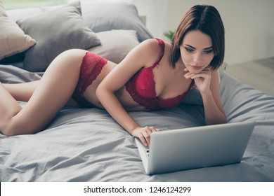 Portrait of nice cute lovely attractive winsome delicate fit slim thin girl wearing red maroon lingerie lying on bed linen sheets with laptop in white light room house indoors
