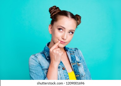 Portrait of nice cute positive pretty cunning girl with two hair-buns, wearing denim jacket, thinking, touching lips with finger, isolated on green turquoise background