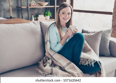 Portrait of nice, cute, positive woman having cup of coffee in hands, covered by plaid, looking to the side, sitting at home in living room, enjoying weekend