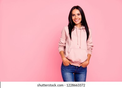Portrait of nice cute sweet lovely lovable attractive adorable winsome charming cheerful glad girl holding hands in pockets isolated over pastel pink background