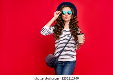 Portrait of nice cute well-groomed lovely attractive cheerful slim romantic wavy-haired lady wearing striped pullover sunhat holding papercup isolated over bright vivid shine red background