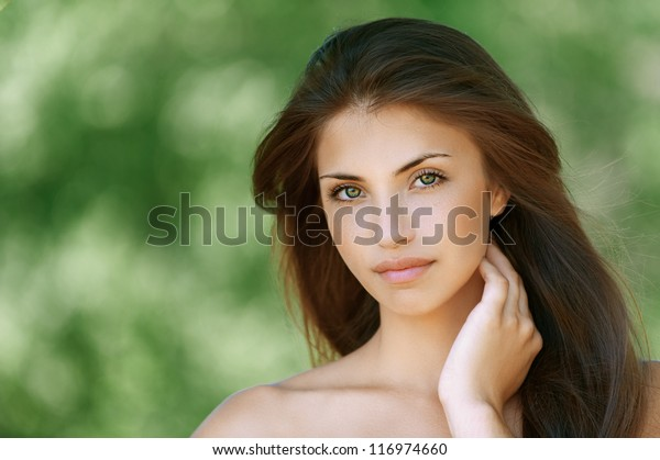 Portrait of nice dark-haired young woman, against background of summer green park.