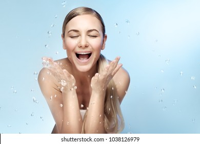 Portrait of a nice excited woman with perfect smile and fresh skin, refreshing her face in the morning with clear cold water, beauty and health care concept, isolated on blue background