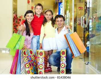 Portrait of a nice family of four with shopping bags looking at camera and smiling