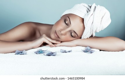 Portrait of a nice female lying down on massage table, closing eyes of pleasure, enjoying day spa, body care and healthy life concept