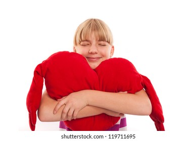 Portrait of a nice girl embracing a red heart plush, isolated on white background