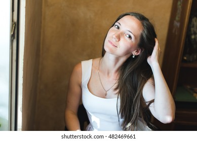 a portrait of a nice girl fixing her hair looking straight into the camera