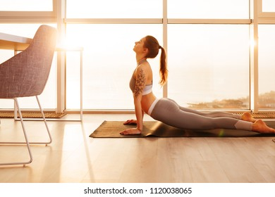 Portrait of nice girl in sporty top and leggings practicing yoga on yoga mat at home with big beautiful windows on background