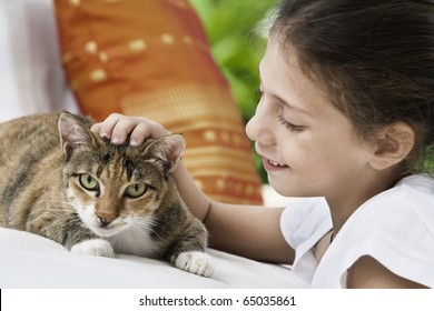 portrait of nice little girl with cat  in summer environment