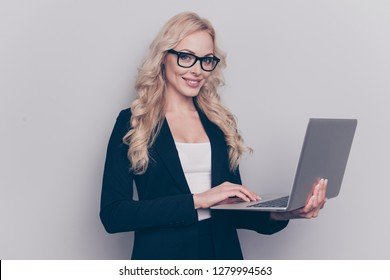 Portrait of nice lovely gorgeous attractive clever smart intelligent cheerful wavy-haired lady eyeglasses eyewear holding in hands laptop isolated over gray pastel background