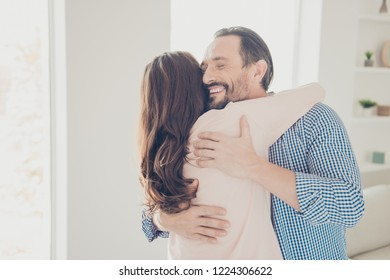Portrait of nice lovely sweet adorable beautiful charming stylish cheerful bearded guy in checkered shirt hugging lady having fun in modern light apartments