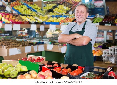 Portrait of nice man seller who is standing on his workplace in supermarket