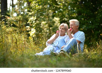 Portrait of nice mature couple eating apples in summer park