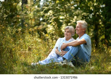 Portrait of nice mature couple sitting on green grass in summer park