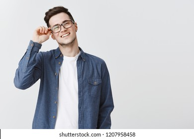 Portrait of nice modern and handsome male student in glasses and blue shirt touching frame of eyewear smiling friendly and delighted, satisfied with productive team work on project over gray wall