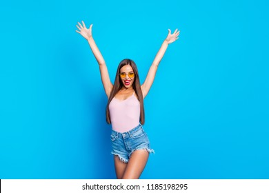 Portrait of nice positive cheerful optimistic cocky attractive adorable straight-haired girl wearing yellow sunglasses, tanktop, shorts, raising hands up, isolated over bright vivid blue background