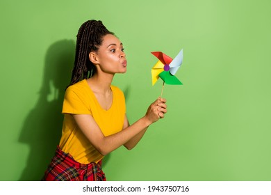 Portrait of nice pretty funny girl blowing paper propeller mill isolated over bright green color background