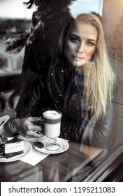 Portrait of a nice but sad woman drinking coffee in the cafe, alone thoughtful beautiful girl in depression, bad mood and unhappiness concept