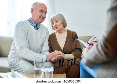 Portrait of nice senior couple holding hands visiting psychologist sharing problems in therapy session