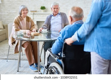 Portrait of nice senior couple smiling at friend in wheelchair coming to meet in retirement home living room