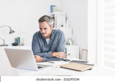 Portrait of a nice smiling grey hair man with beard holding his glasses, working at home on some project, he is sitting at a white table looking at his laptop in front of him. Focus on the man