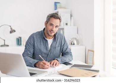 Portrait of a nice smiling grey hair man with beard, working at home on some project, he is sitting at a white table looking at camera, writing ideas with his laptop in front of him. Focus on the man