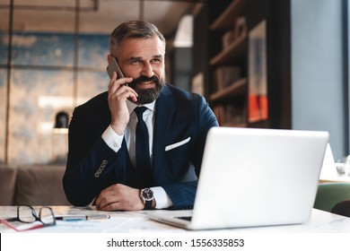 Portrait of a nice smiling man with beard, he is sitting at table, talking on the phone with his laptop, tablet, notebook