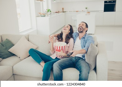 Portrait of nice stylish cheerful girl and guy wearing denim jeans sitting on comfortable couch divan sofa in studio kitchen living room enjoying laughing in white modern apartments