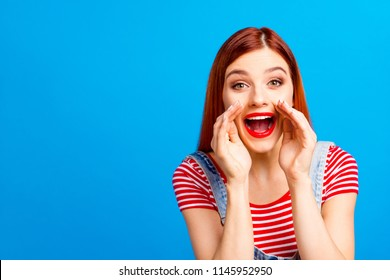 Portrait of nice vivid girlish red straight-haired happy young girl with opened mouth, announcing big sale, isolated over blue background, copy space