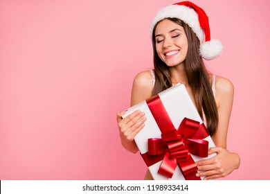 Portrait of nice winsome delighted positive cheerful magnificent sweet straight-haired lady in lingerie and hat, holding, keeping big white gift box, isolated over pink pastel background