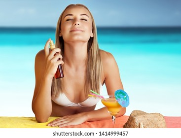 Portrait of a nice woman on the beach using spf spray, applying sunscreen to protect her skin from sunburn, happy and healthy stay on the beach