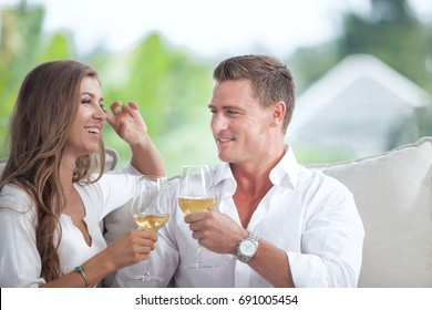 portrait of nice young couple drinking wine in summer house environment