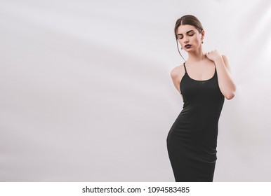 Portrait of nice young gorgeous woman on gray solid backgrounds. To a lots of copy space.