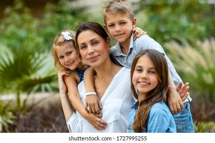 Portrait of a nice young mother with pleasure spending time with her three precious kids in the spring park, having fun together, big happy family enjoying life